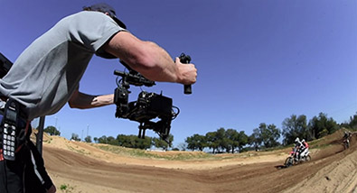 Photo of a video camera operator with a camera in a rig, shooting a dirtbiker on a track