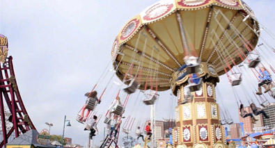 Photo of an amusement park swing ride with people on it