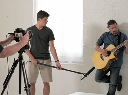 Photo of a guitar player leaning against a wall, a sound person with a mic on a boom, and a camera operator's hands on the camera, shooting