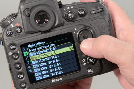 Photo of a hand on a Nikon D-SLR with the movie settings screen on the LCD