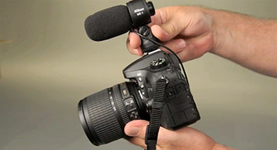 Photo of a person's hands holding a Nikon D-SLR with the ME-1 mic on the hotshoe