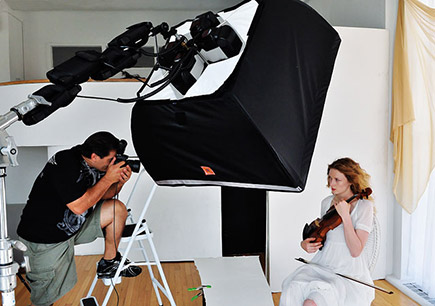 Photo of a photographer shooting a woman holding a violin, in a studio with a softbox